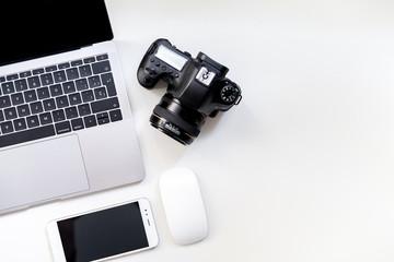 Vista del escritorio y espacio de trabajo con la cámara smartphone y portátil de un fotógrafo profesional y diseñador gráfico