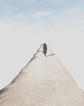 Woman walking along a path towards the sky, South Korea