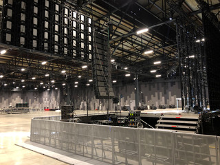 Installation of professional sound speakers, line array and stage equipment for a concert. Backstage area and tech zone with metal barriers. - fototapety na wymiar