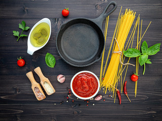 The thin spaghetti on black wooden background. Yellow italian pasta with ingredients. Italian food and menu concept.