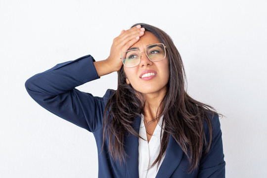 Stressed young businesswoman in eyeglasses. Disappointed businesswoman in formal wear holding hand on forehead and looking away isolated on grey background. Emotion concept