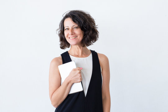 Positive smiling woman with tablet posing over white background. Happy middle aged woman holding digital device and smiling at camera. Computer technology concept