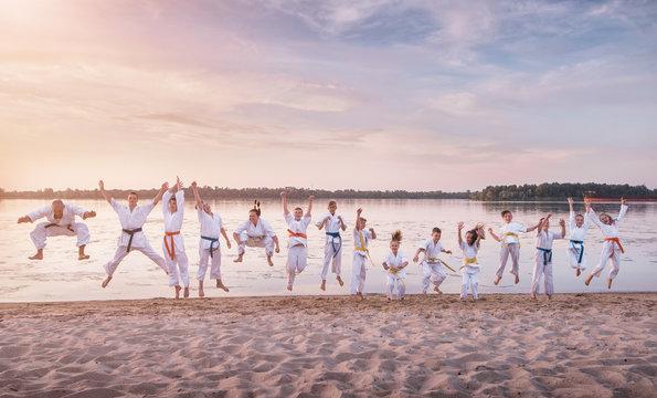 Funny jumping people. Karate kids team on sunset beach