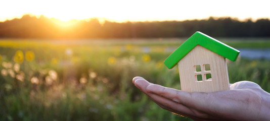 Wooden house in the hands in the sunset background. Real estate concept. Eco friendly home. Symbol of happy family life. Buy a housing outside the city. Search for hotel on vacation. Selective focus Wall mural