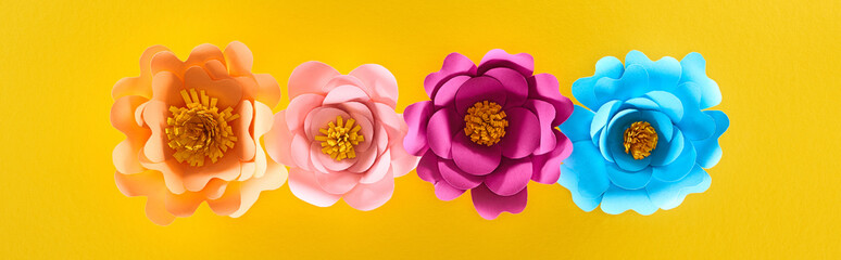 flat lay with paper cut multicolored bright flowers on yellow background, panoramic shot