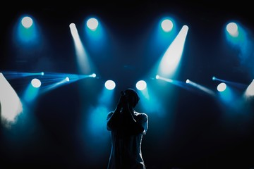 Rap singer with microphone on stage in music hall.Silhouette of hip hop singer with mic in hands singing a song on scene in blue lights.Young pop musician sings popular song on stage in music hall