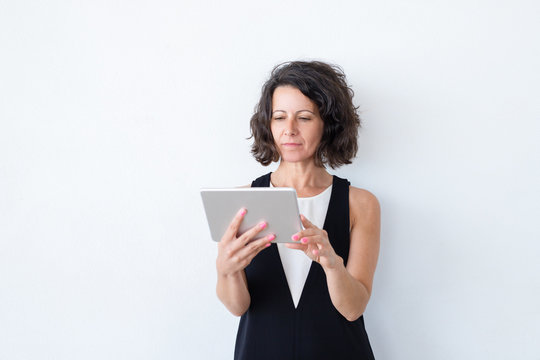 Serious focused woman in casual using tablet. Curly haired middle aged model standing over white background and reading on screen. Tablet using concept
