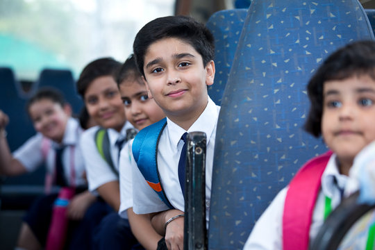 School children traveling in school bus looking at camera