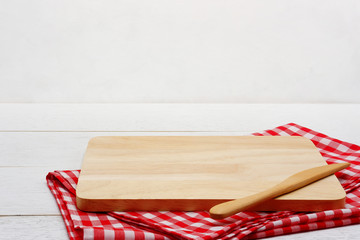 Empty rectangle wooden serving board with butter knife and red gingham tablecloth on white wooden table.