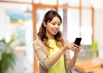 technology and people concept - happy asian woman using smartphone over office background