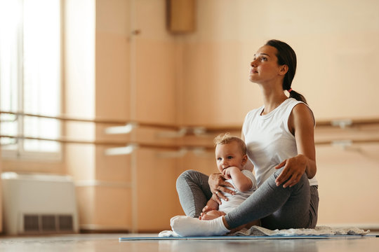 Young mother practicing Yoga with her baby in health club.