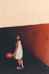 Portrait of young woman with red balloon in hand standing against tunnel . Scary movie concept.