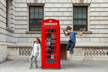 Photo sur Plexiglas Londres Girl is leaning against the phone booth with a smartphone and from the other side a boy leaps with joy.