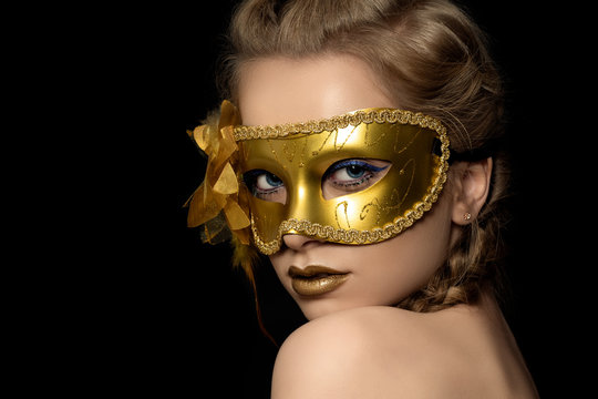 Young beautiful woman wearing golden party mask