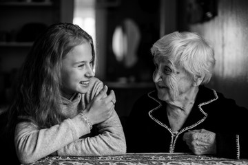 A little cute girl with a grandmother in the house black and white photo.