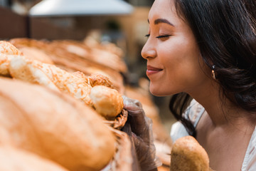 Fototapeta selective focus of cheerful asian woman smiling while smelling bread in supermarket