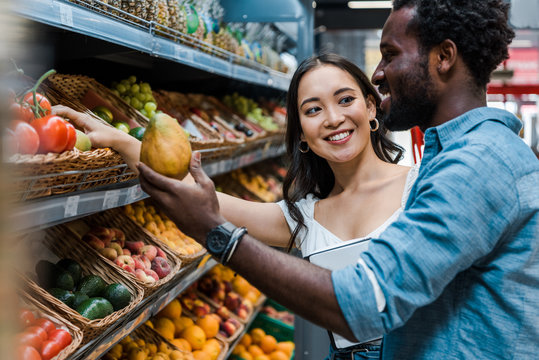 happy asian woman looking at african american man near fruits in store