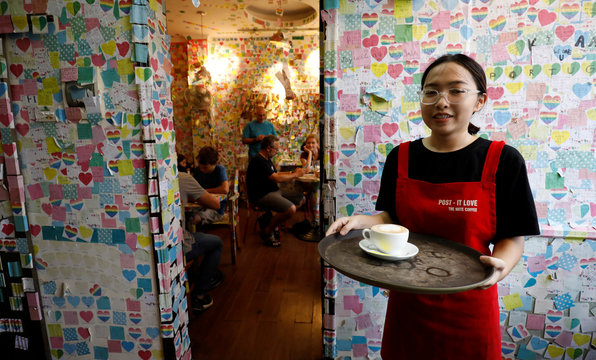 An employee holds a tray at the Note Coffee shop which walls, ceiling and chairs are covered with post-it notes from people around the World, in Hanoi