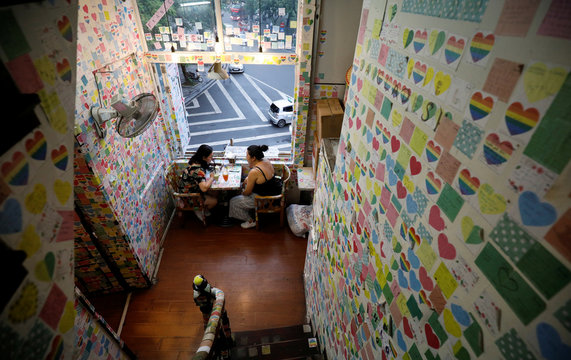 Customers sit at the Note Coffee shop which walls, ceiling and chairs are covered with post-it notes from people around the World, in Hanoi