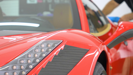 In the car center (in the garage), professionals polish a new sports car. Luxury car polishing. Concept of: Racing, Sport car, New, Slow motion, Nascar, Red, Chrome plated.