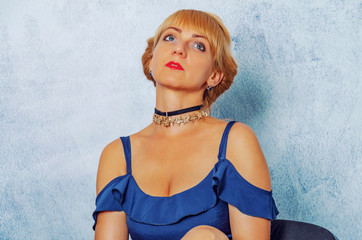 Blond woman in a blue dress is sitting on a chair against a background of a wall with plaster.