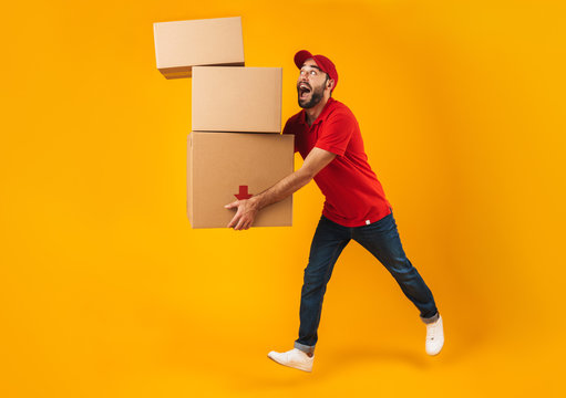 Full length portrait of funny delivery man in red uniform carrying falling packaging boxes