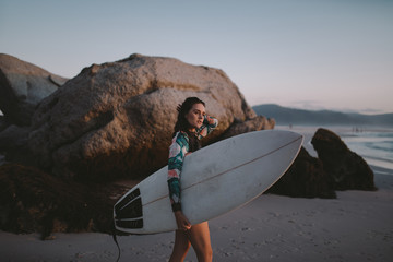Side view of young woman with surfboard walking on beach