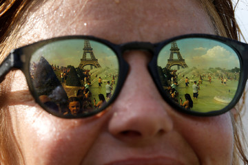 People cooling off in the Trocadero fountains across from the Eiffel Tower are reflected in sunglasses in Paris