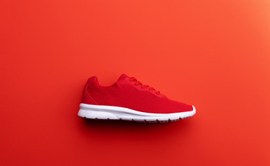 A studio shot of running shoe on red background. Flat lay.