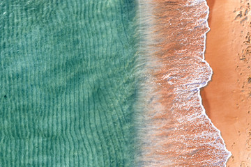 Sandy seashore with turquoise green sea water. Small waves on the beach.