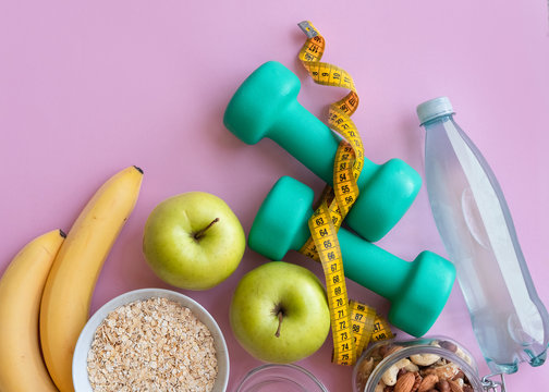 Fitness background with bottle of water, apple, dumbbells, nuts, and tape measure on pink table