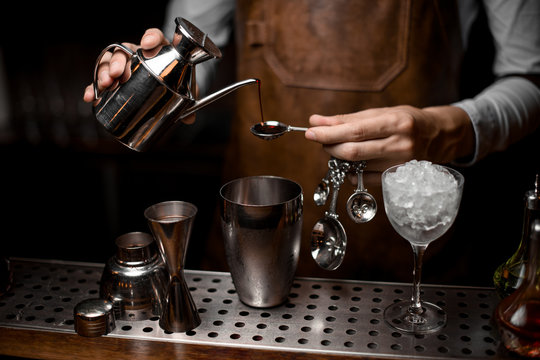 Bartender preparing drink with kettle, spoon and shaker