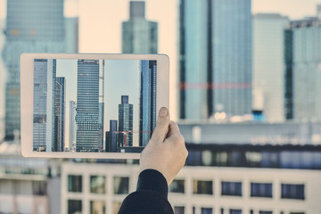 Germany, Frankfurt, hand taking photo of financial district with tablet
