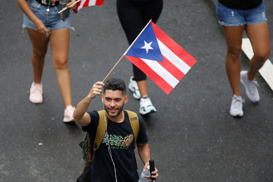 A man waves a Puerto Rican flag during a rally to celebrate the resignation of Puerto Rican Governor Ricardo Rossello in San Juan