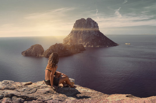 Amazing seascape view with a girl looking ahead to the magic rock of Es Vedra Island at sunset. Summertime in Cala d'Hort, Ibiza, Balearic Islands.