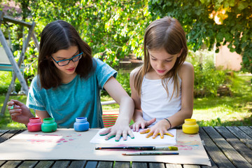 Sisters printing colour on sheet of paper with their hands