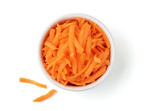 Fresh organic shredded carrots in small white bowl. Raw grated carrots isolated on white with clipping path. Top view or flat lay.