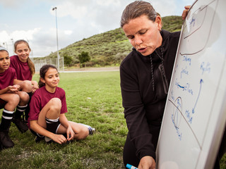 Girls looking at coach writing over whiteboard while planning on field