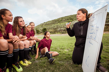 Female coach talking to girl while discussing strategy for during sports match on field