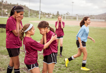 Girl consoling crying team mate during failure in soccer match