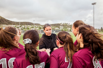 Girls in sports uniform standing with coach during discussion on field against sky