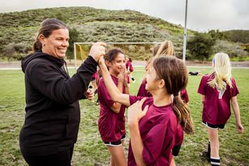 Female coach holding girl's hand during celebration on soccer field