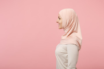 Side view of smiling beautiful young arabian muslim woman in hijab light clothes posing isolated on pink wall background, studio portrait. People religious Islam lifestyle concept. Mock up copy space.