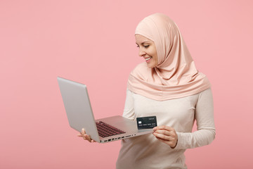 Pretty arabian muslim woman in hijab light clothes posing isolated on pink background. People religious Islam lifestyle concept. Mock up copy space. Hold and work laptop pc computer, credit bank card.