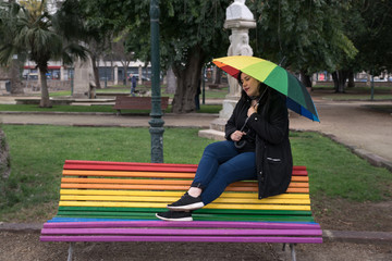 Woman  sitting on rainbow bench with rainbow umbrella in the rain