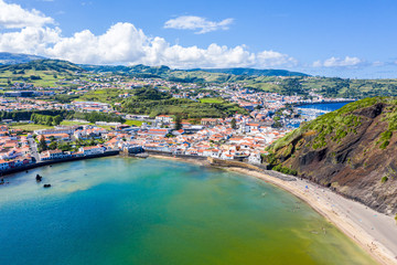 Gates Portao, idyllic holiday beach Praia and azure turquoise bay Baia do Porto Pim, red roofs of historical touristic Horta town centre, mount Monte Queimado, Faial island, Azores, Portugal