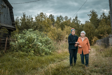 Two senior women are standing arm in arm at their old garden