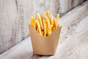 Close up view on Potatoes French Fries in Carton Package Box Isolated on wooden background. Fast food concept mock up. Blank kraft or craft paper cardboard with french fries fry