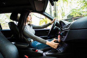Young woman shifting gears on gearbox and driving car