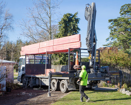Builders unload roof trusses that have been delivered by a Hiab truck to a building site